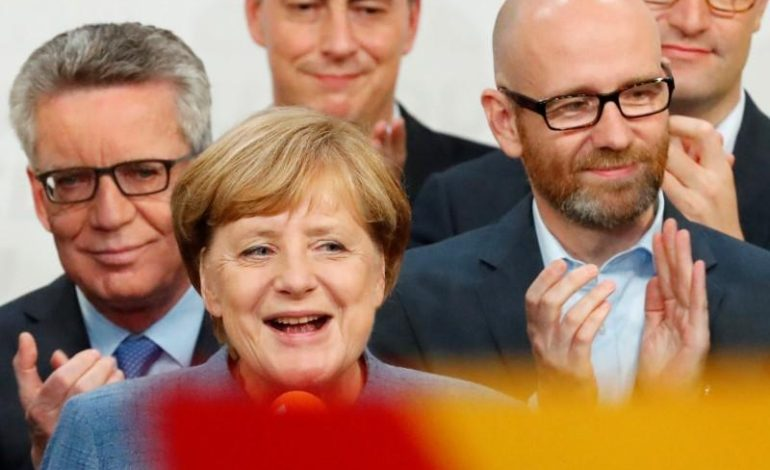 Germany's Merkel hangs on to power but bleeds support to surging far right