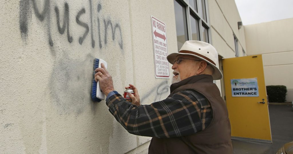 Tom Garing cleans up racist graffiti painted on the side of a mosque in what officials called an apparent hate crime, in Roseville, Calif. Feb. 1, 2017. File photo y AP