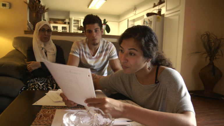 Assia Boundaoui shows FBI documents to her family in The Feeling of Being Watched.