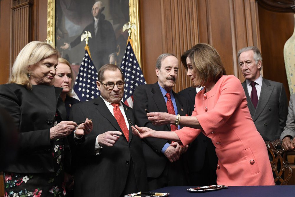 Speaker Pelosi hands out pens after she signs a resolution to transmit the two article of impeachment to the Senate on Wednesday