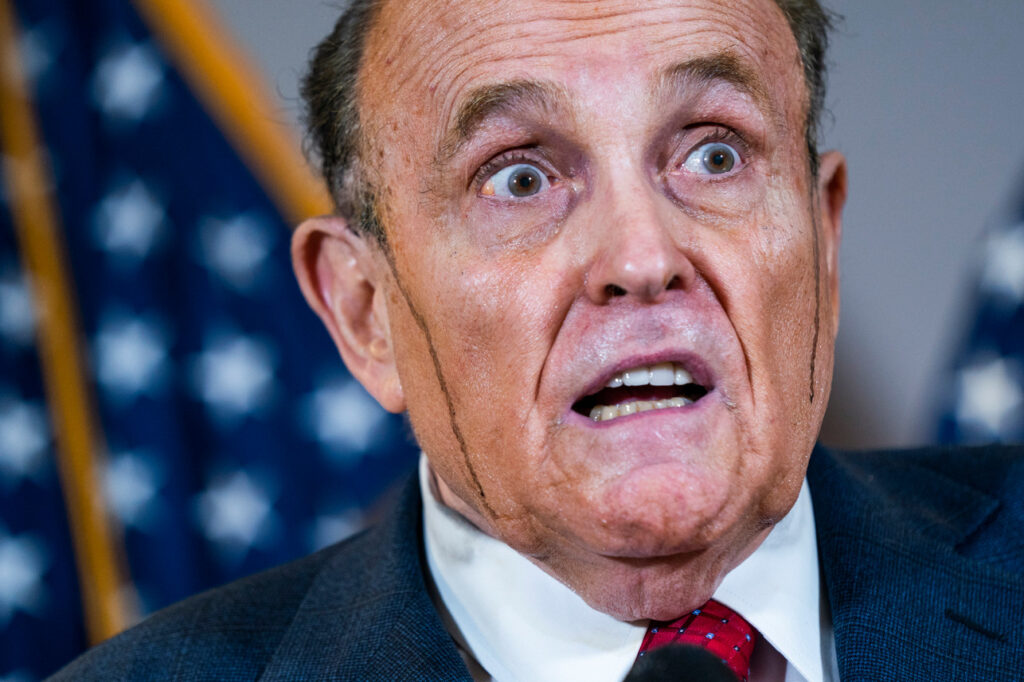 Trump's lawyer Rudy Giuliani speaks to reporters, with hair dye running down his face, on Thursday. Photo: EPA