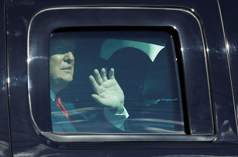 President Donald Trump waves from a car as he drives past supporters in West Palm Beach, Florida, January 20, 2021. REUTERS/Marco Bello