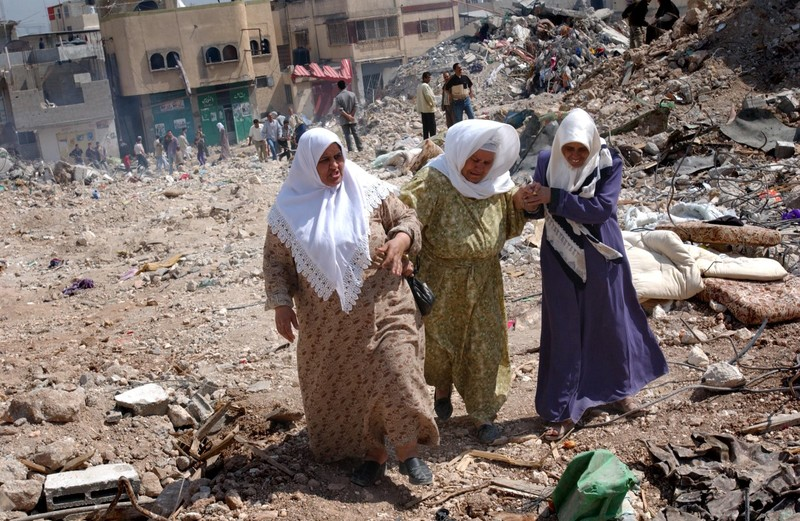 Women whose house was destroyed by the Israeli troops during fighting in the Jenin refugee camp, return to the rubble of their homes after the Israeli army pulled back to positions outside the camp April, 2002. Photo via KRT