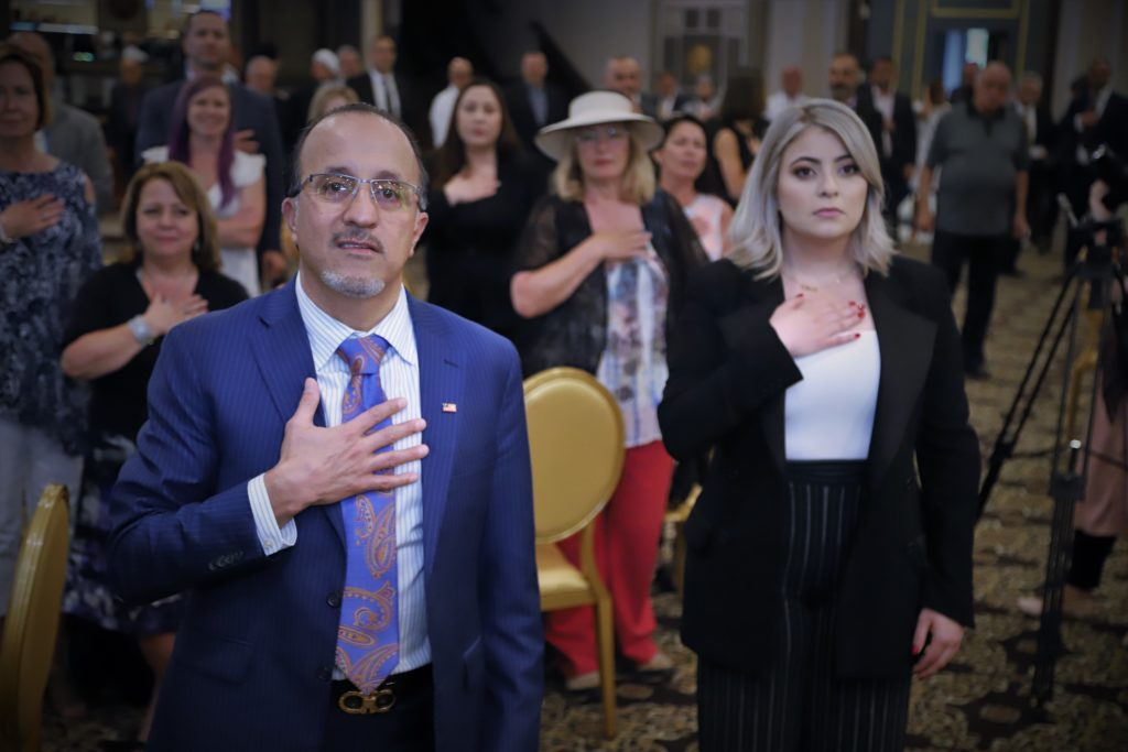 Councilman Dave Abdallah pays respect to the national anthem beside his daughter during the fundraising event at the Bellagio Banquet Center in Dearborn Heights, Wednesday, June 12 - Photos by Abbas Shehab