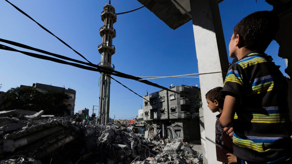 Palestinian boys look at the rubble of al-Qassam mosque, hit by an Israeli airstrike on Saturday, as they stand in the bedroom of their destroyed family house in Nusseirat refugee camp in the central Gaza Strip on Sunday, Aug. 10, 2014. Photo by AP