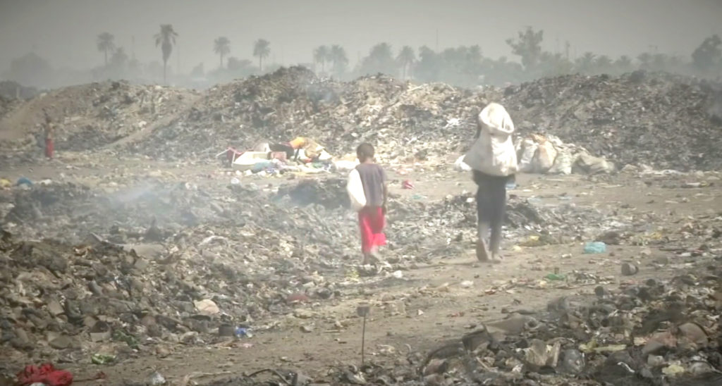 Two Iraqis walking next to piles of garbage in southern Iraq