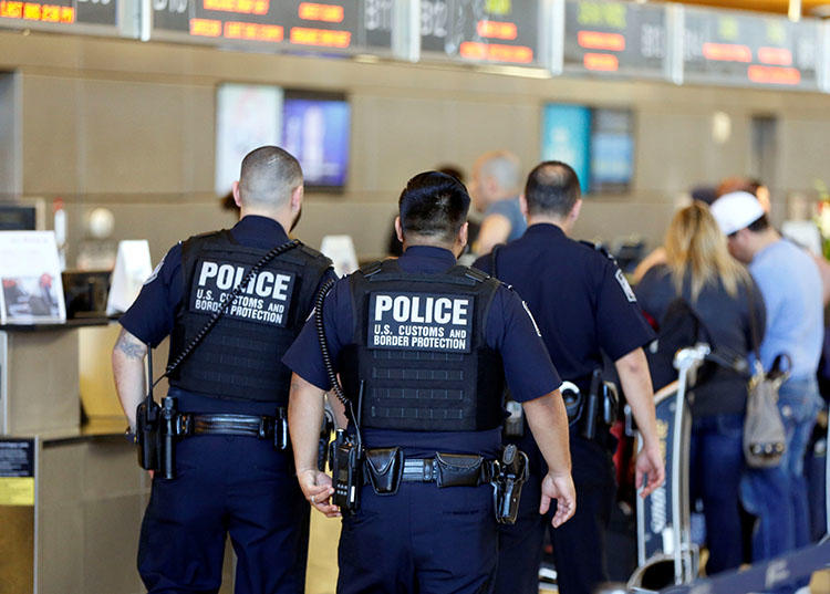 Officers with the U.S. Customs and Border Protection walk past ticket counters.