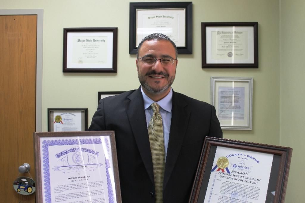 Youssef Mosallam holding certificates of recognition for his academic work in Dearborn Public Schools