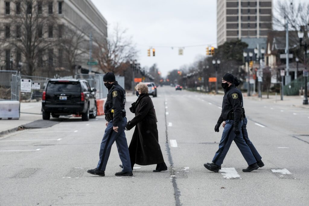 An electoral voter is escorted by Michigan State Police in Lansing on Dec. 14. Photo: Matthew Hatcher/Bloomberg