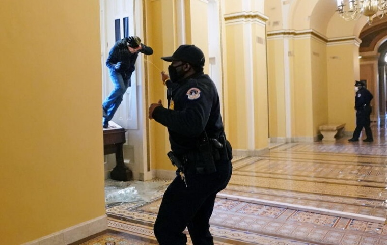 A U.S. Capitol police officer shoots pepper spray at a protestor attempting to enter the Capitol building during a joint session of Congress to certify the 2020 election results on Capitol Hill in Washington, U.S., Jan 6.