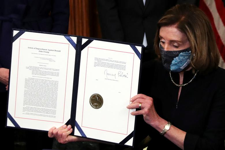 House Speaker Nancy Pelosi shows the article of impeachment against President Trump after signing it in an engrossment ceremony at the U.S. Capitol, Jan 13. Photo: Leah Millis