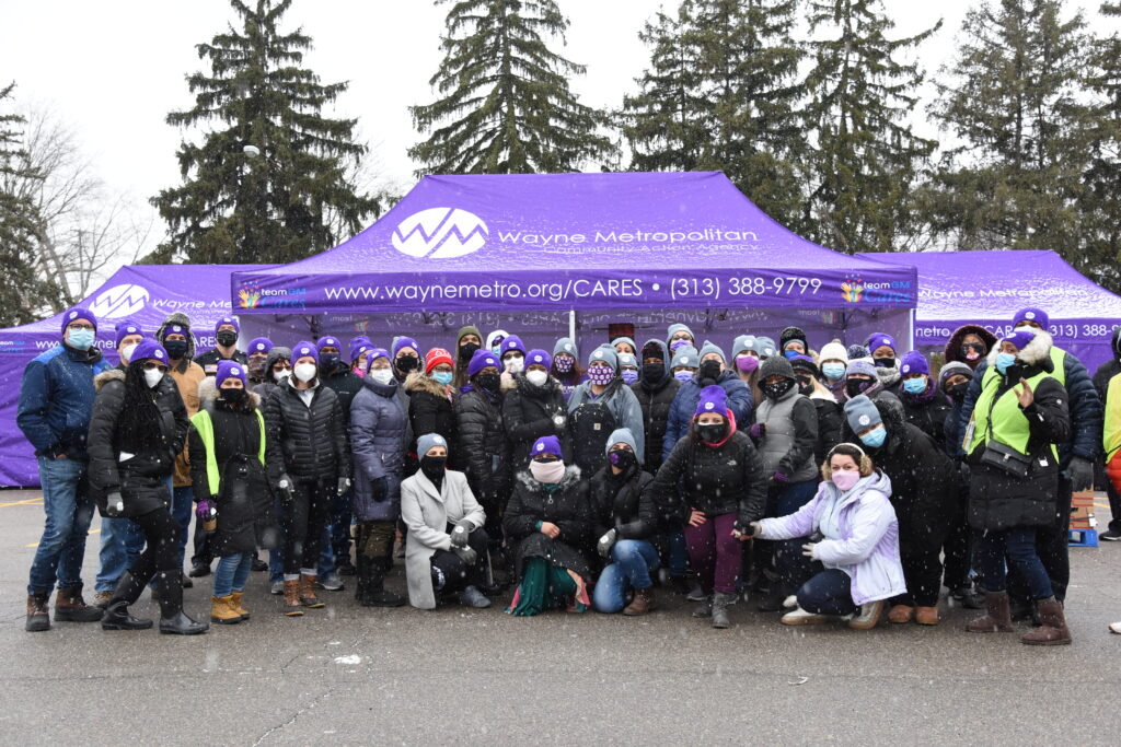 At a distribution drive in Dearborn Heights, Wayne Metro Staff and volunteers pose in front of distribution tents designed and supplied by GM to protect them from the elements